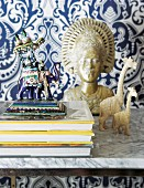 Animal figurines and gilt bust on marble shelf against blue and white patterned wallpaper