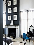Drawings of trees in black frames hung on black chimney breast above pale marble mantelpiece in grand bedroom