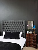 Double bed with quilted headboard against wall in tone-on-tone anthracite combined with white bed linen and black throw; antique bedside table to one side