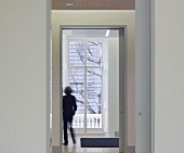 View through an open door and passageway of a lady standing in front of a balcony door (Goethe Institut, London)