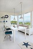 Weisser Esstisch und Klappstühle aus Holz am Fenster mit Ausblick
