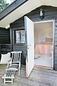 Liegestuhl auf Veranda eines Wochenendhäuschen aus Holz neben offener Tür und Blick auf das Bett