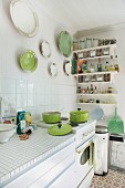 Sunny kitchen with retro cooker and collection of white and green china plates on wall