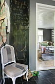 Handwritten congratulations on blackboard behind renovated chair with silver stripe in hallway with black tiled floor