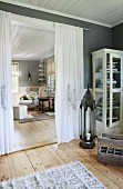 Airy curtain as partition next to display cabinet full of books behind large lantern
