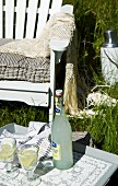 Tray set with refreshing drinks in long grass in front of white garden chair