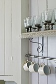 Glasses on wall-mounted shelf with lace trim above cups hanging on rail in corner of white, wood-panelled kitchen