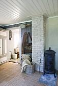 Scandinavian room with antique log burner, brick chimney, baskets and cloakroom area