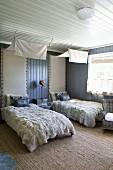 Doppelzimmer mit gemütlichen Felldecken und Kissen auf den Betten, darüber abgehängte weiße Stoffbahnen als Baldachine, Rückenlehne an der Wand gepolstert