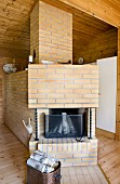Brick open fireplace with birch logs stacked in copper bucket