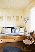 Pale wood sofa bed with white and blue patterned textiles
