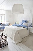 Bright, pale bedroom in white with blue accents and antique birdcage