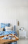 Breakfast tray on white bed with blue and white bed linen and linen scatter cushions