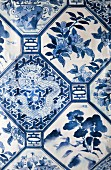 Blue and white bed linen with Chinese-style geometric pattern of flowers, trees and dragons