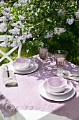 Garden table in sunshine with violet linen tablecloth and china crockery of the same shade below flowering lilac