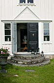 Entrance of traditional Swedish wooden house with round steps leading to black front door