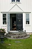 Eingang eines traditionellen schwedischen Holzhauses mit runder Eingangstreppe und schwarzer Eingangstür