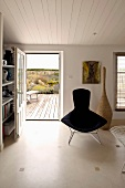 Classic armchair, upholstered in black in front of a open terrace door in a simple living room with white wood ceiling