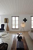 Wohnraum in eklektizistischem Stil - Stuhl aus 50er Jahren und rustikaler Couchtisch vor zeitgenössischer Stehlampe