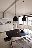 Retro hanging lamps above a dining table with a black top and chairs with white metal frames in a functional kitchen