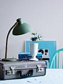 Blumensträusschen auf Vintage-Koffer mit Tischlampe und Bücherstapel