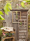 Old wooden shed decorated with vintage picture frames and flowers in front of brick wall