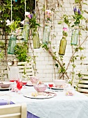 Flower arrangements hung above set terrace table