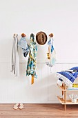 Various accessories (cloak, clothing, hat, bag) hanging on wooden wall hooks