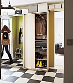 Modern hall with ample storage space in wardrobe with mirrored, sliding door; woman reflected in mirror