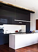 Tall fitted kitchen with glossy, black doors and white counter below suspended strip light