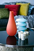 Artistic, coloured glass vases and small, finely ornamented beakers on dark, steel and glass table; scatter cushions in blurred background