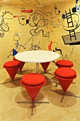Modern, plywood paneled conference room with a white, round table and stools upholstered in orange fabric in front of a trendy wall decorated with cartoons (Red Bull Zentrale, Amsterdam)
