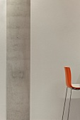 Orange bar stool with chrome legs in front of a white wall with concrete pillars (Bibliothek Hoofddorp-Centrale)