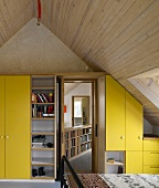 Contemporary, attic bedroom with a wood ceiling and yellow closets (Four Oaks Brick House in the Country)