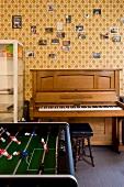 Tischfussball gegenüber Klavier an Wand mit gemusterter Tapete