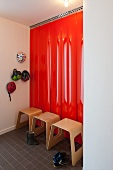 Modern wooden stools against red lacquered panels and cycle helmets hung on wall