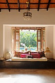 Floor cushions and scatter cushions on wooden platform below open window with shutters and view of pool in garden