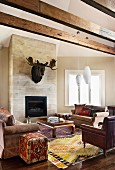 Classic-style area around modern fireplace below magnificent moose head - colourful mixture of styles with Oriental rugs and pouffes