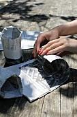 Frauenhände mit roten Fingernägeln wickeln Gläser in Zeitungspapier ein