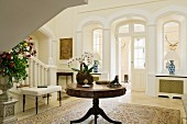 Round wooden table next to foot of staircase and arched doorway in foyer of English stately home