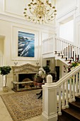 Grand foyer with staircase and modern artwork on white, wood-panelled wall above open fireplace