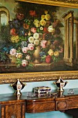 Floral painting with gilt frame above antique wooden console table