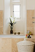Renovated bathroom with pale stone tiles on wall and bathtub and orchid in window niche