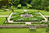 View down onto stately gardens with topiary hedges and geometric beds