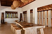Luftiger Essbereich mit rustikalem Holztisch mit Hockern; über dem Tisch exotische Lampen aus Naturmaterialien
