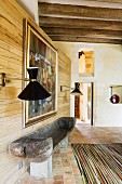 Hand-crafted bench against wooden wall with retro sconce lamps in interior of country house