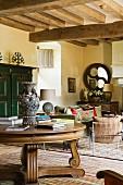 Antiker, runder Holztisch vor Loungebereich in mediterranem Landhaus mit Holzbalkendecke