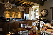 Finnish, designer pendant lamps made from wooden slats above kitchen counter and set dining table in rustic ambiance