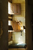 Split window shutters and sconce lamps on stone wall
