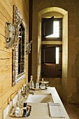 Ornate mirror flanked by sconce lamps on wooden wall above perfume bottles on washbasin; window niche with half-open interior shutters in background